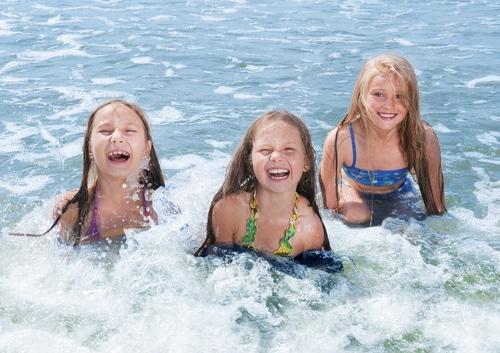 Lachende Kinder im Meer